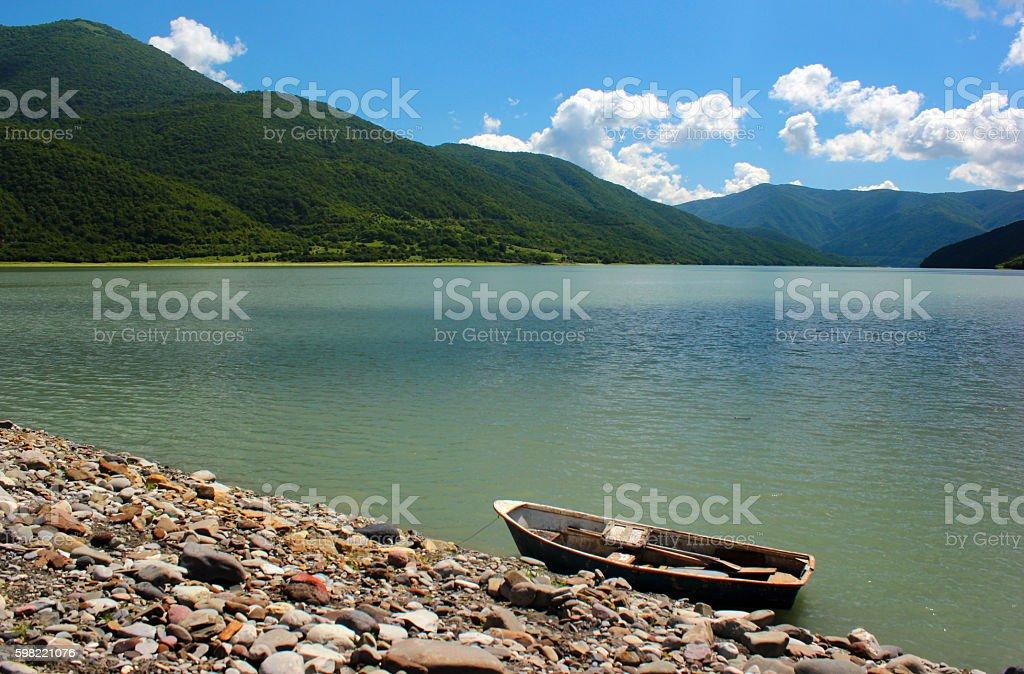 Lone punt boat on rocky lake shore stock photo