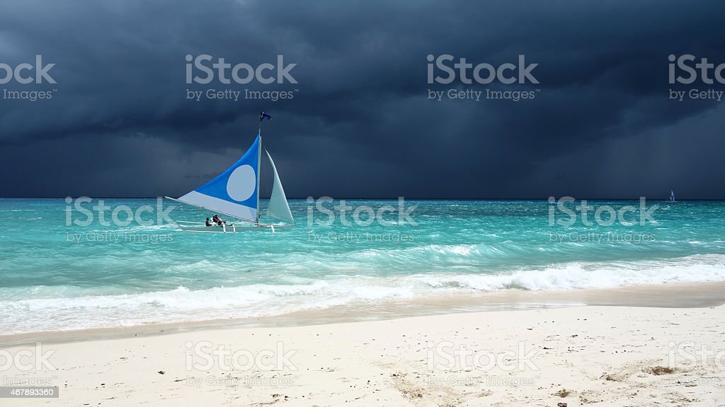 Lone sail boat braves an approaching tropical storm stock photo