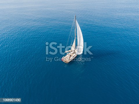 A lone sailing boat at anchor aerial view