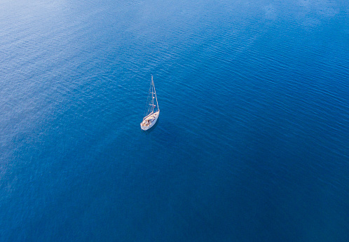 A lone sailing boat at anchor. The view from the air. Drone photo