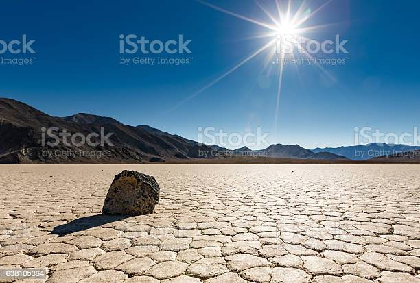 """A lone """"sailing rock"""" sits basking in the bright unrelenting sun at Racetrack Playa in Death Valley National Park, California"""