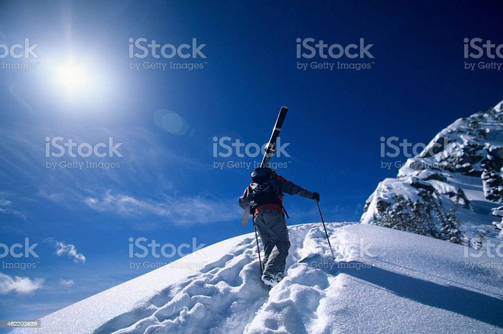 Lone skier hiking up mountain summit with full ski gear stock photo
