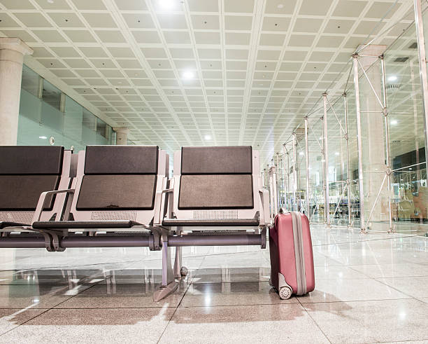 lone suitcase in waiting area stock photo