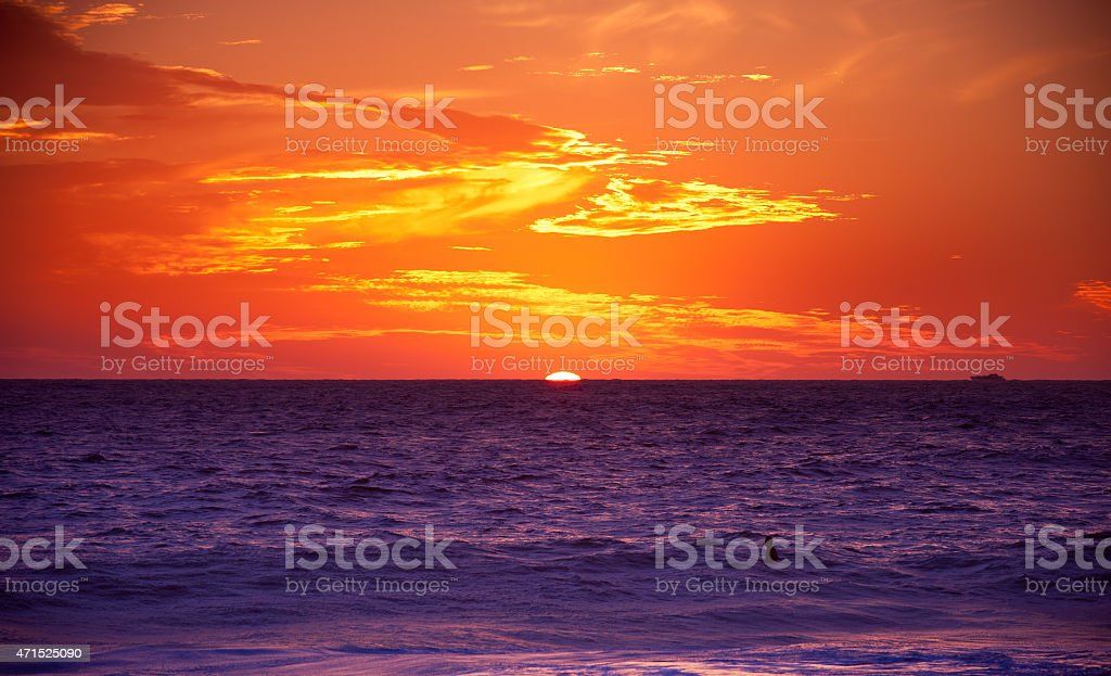 Lone surfer and intense red gold sunset sky stock photo