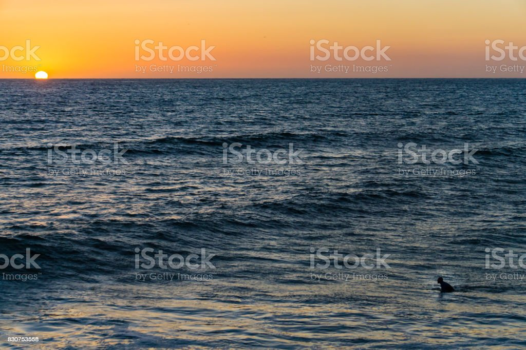 Lone Surfer at Sunset stock photo