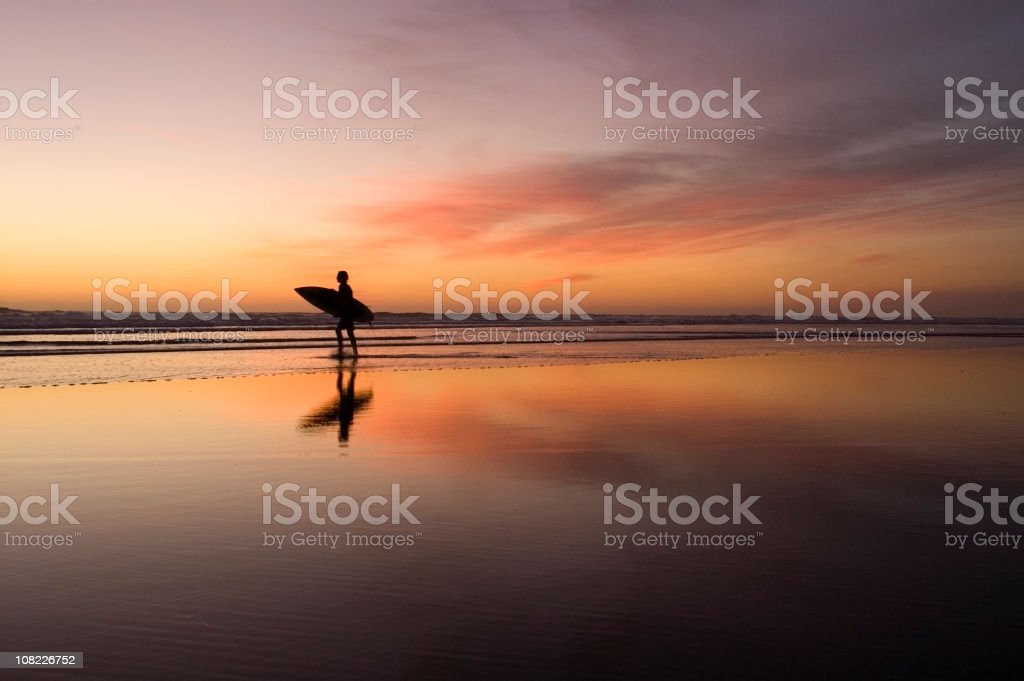 Lone surfer on beach at sunset royalty-free stock photo