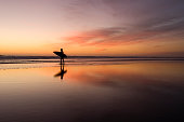 A surfer walks along a spectacular sunset reflection. Auckland, New Zealand.\n\nFurther surf images in my portfolio, please have a look around.