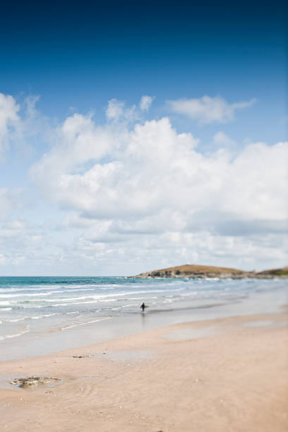 lone surfer on fistral beach - cornwall stock pictures, royalty-free photos & images