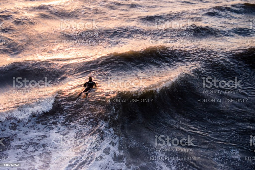 Lone surfer waiting for waves in frigid choppy Pacific Coean stock photo