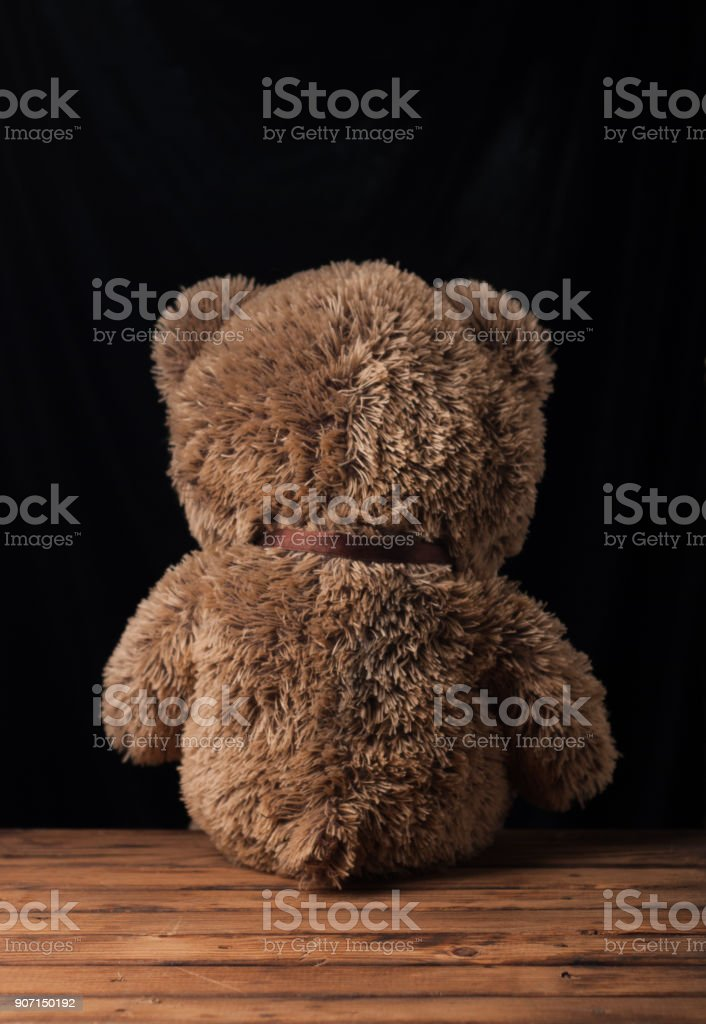 A lone Teddy bear sits on a wooden surface, stock photo