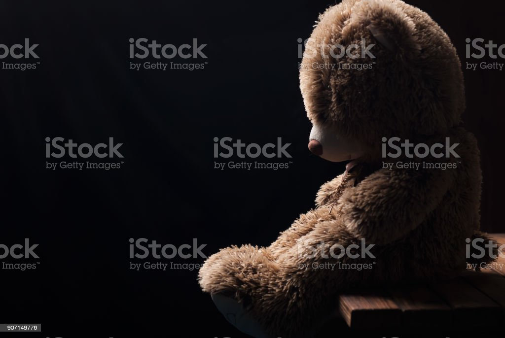 A lone Teddy bear sitting in the dark, side view, stock photo