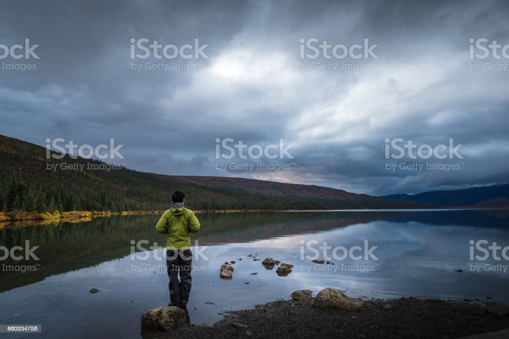 lone traveler in front of lake stock photo