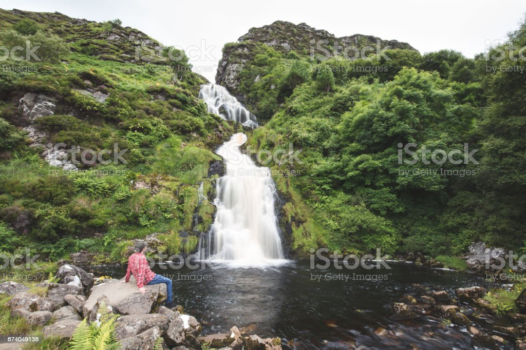 Lone walker at Assarancagh Waterfall, Adara. County Donegal, Ireland royalty-free stock photo