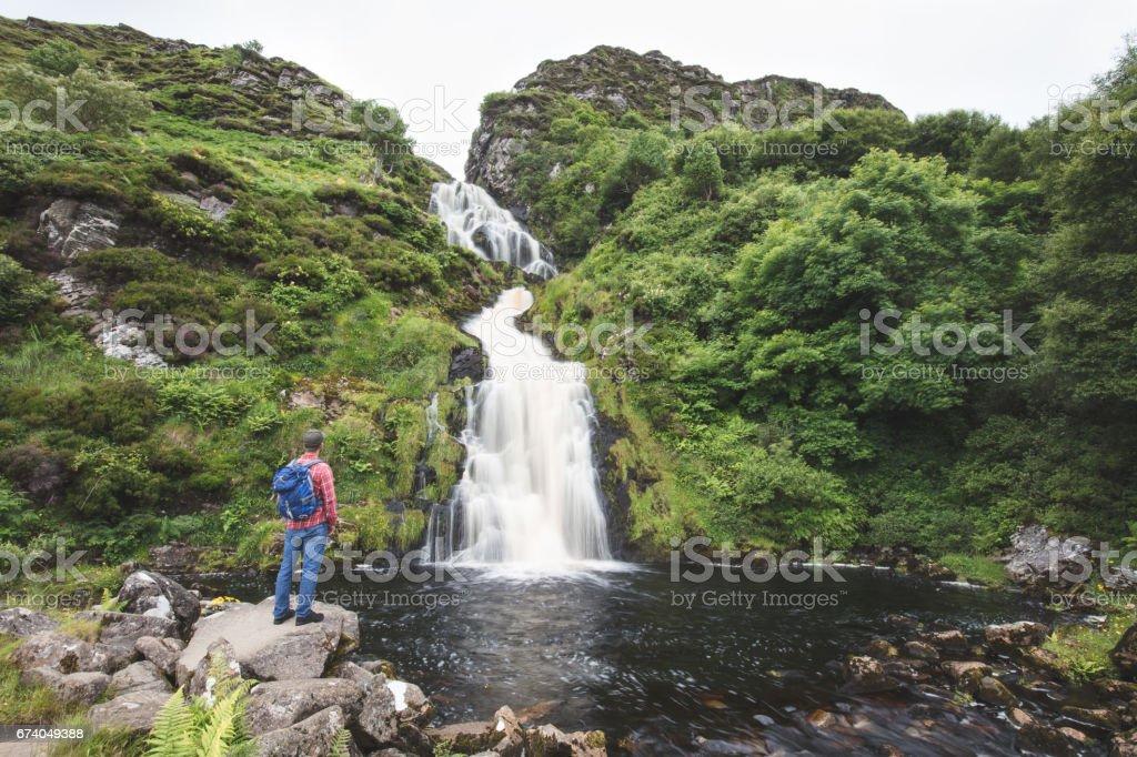 Lone walker at Assarancagh Waterfall, Adara. County Donegal, Ireland royalty-free stock photo