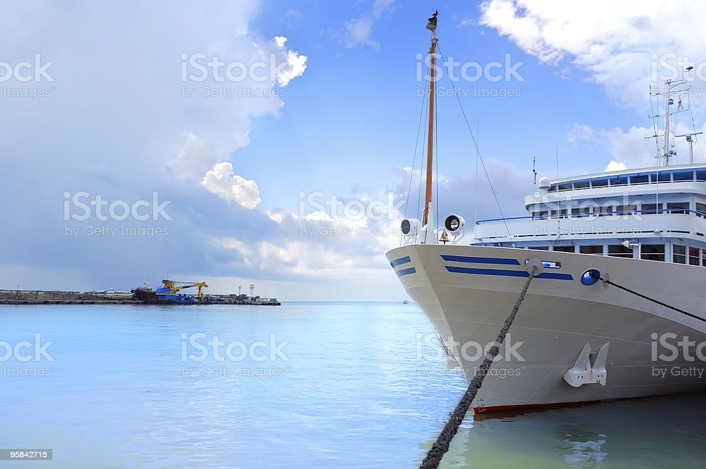 Lone white boat tied anchored to the dock in the blue sea royalty-free stock photo