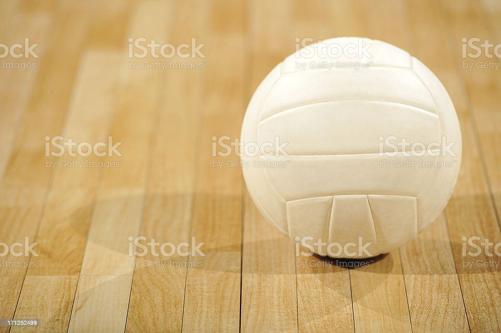 A lone white volleyball sitting on a wooden floor stock photo