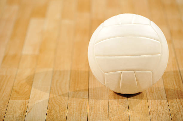 a lone white volleyball sitting on a wooden floor - volleyball stock photos and pictures