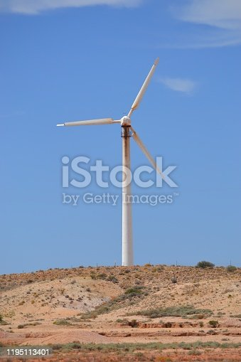 Single turbine set against a blue sky powering outback town of Coober Pedy