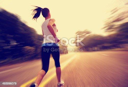 502412594 istock photo Lone woman athlete running on road 493996079