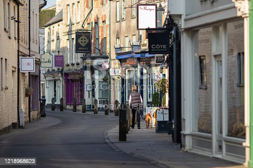 10the April, 2020 - Lone woman walking her dog down the deserted quaint Black jack street in Cirencester, Gloucestershire during the Coronavirus outbreak during Spring 2020