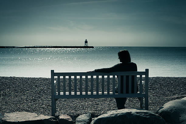 Lone Woman, Widowed, Divorced, or Lonely, Contemplating Grief, Sadness, Depression Woman in silhouette, sitting on a bench in a moody landscape at water's edge. The lone woman may be widowed, divorced, or lonely, sitting in solitude, contemplating her grief, sadness, or depression. The lighthouse in the distance is a symbol of finding hope or direction in a sea of troubles. mourner stock pictures, royalty-free photos & images