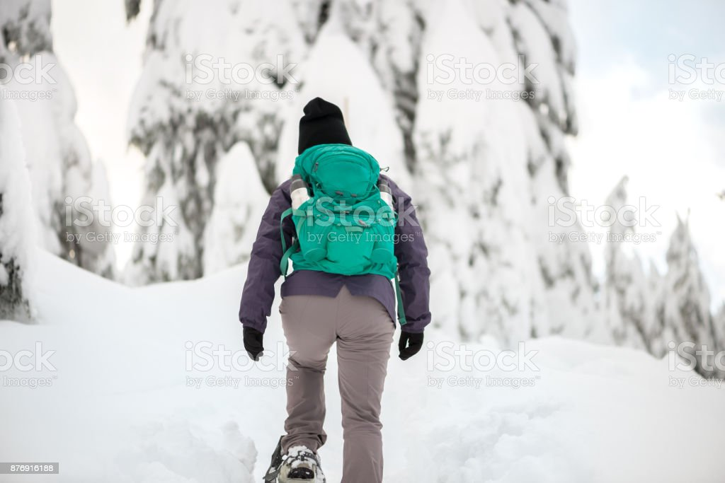 Lone Woman with Backpack Snoweshoeing Up Snow Covered Mountain Forest stock photo