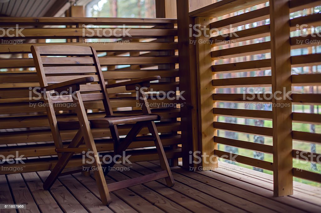 lone wooden chair on the balcony of wood with baffles stock photo