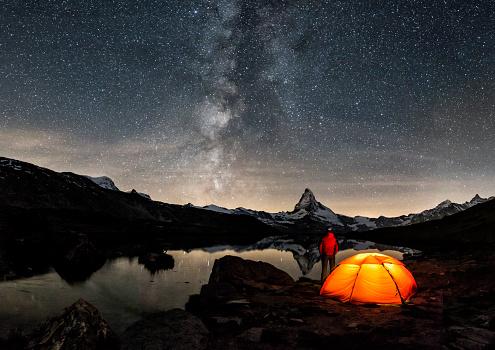 An illuminated tent under Milky Way at Matterhorn in Switzerland