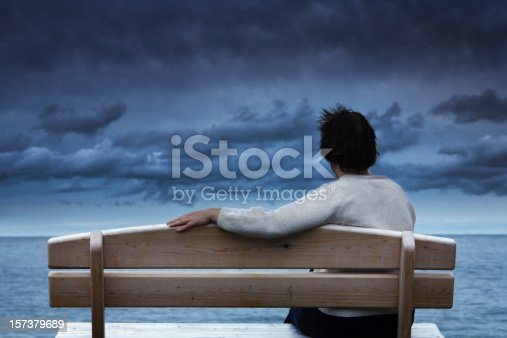 One woman waiting alone on waterfront bench under ominous, stormy sky. Her extended arm along the wooden seat suggests she is forlorn, missing someone. Dramatic, dark, moody empty sea horizon expresses concepts of loneliness, grief, sadness, depression, solitute, contemplation, adversity, and suicide. Rear view of unidentifiable person with copy space.