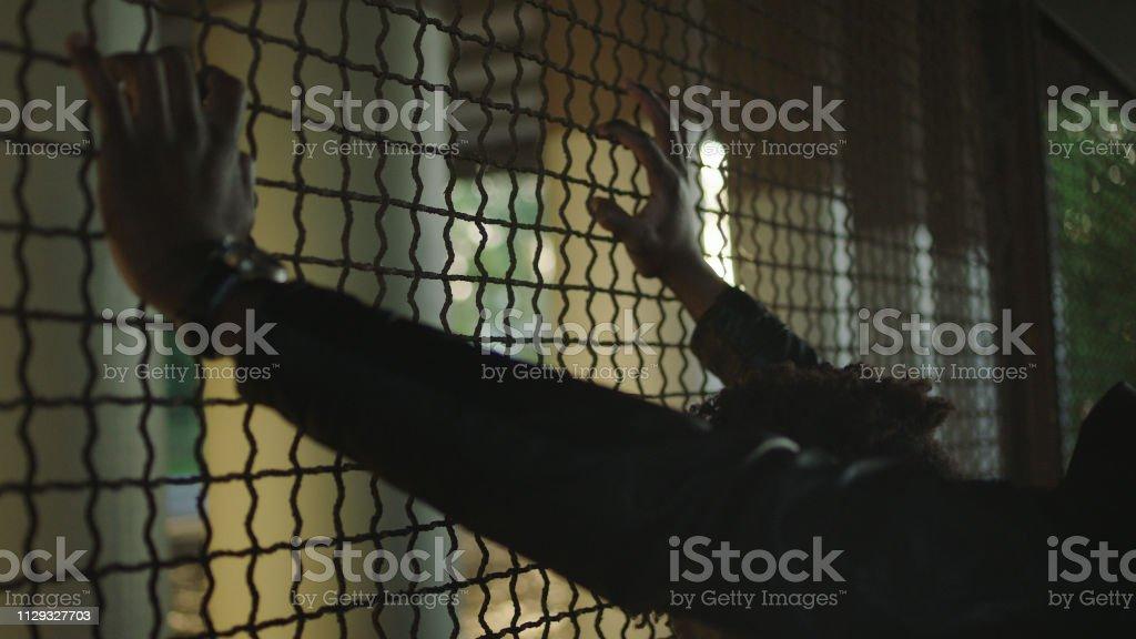 Sad man looking at view. Fence under a bridge.