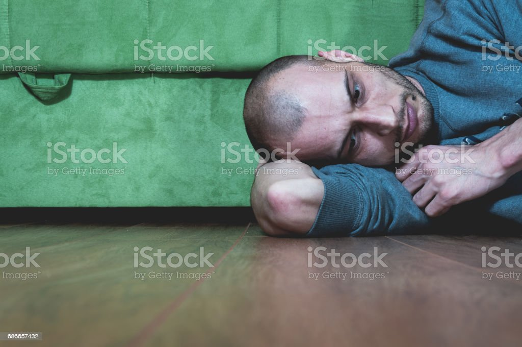 Loneliness. Sadness. Depression. Lonely and depressed man lying on the floor of his home. He is missing someone. royalty-free stock photo