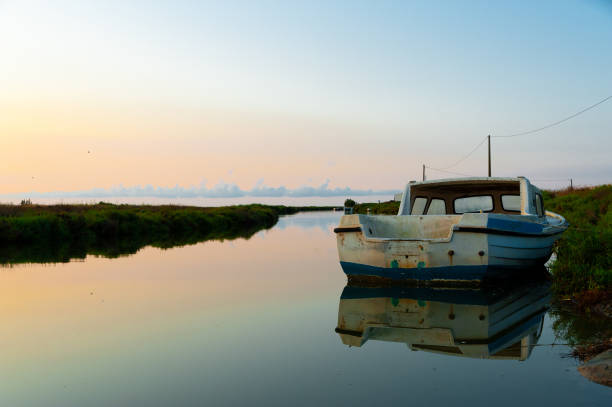 lonely abandoned fishing boat at sunrise in ebro delta park in catalunya, a quiet scene symbol of loneliness and peace of mind stock photo