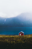 istock Lonely abandoned red house on the meadow with view of the mountains and waterfall in Norway 1190627627