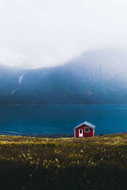 Lonely abandoned red house on the meadow with view of the mountains and waterfall in Norway stock photo