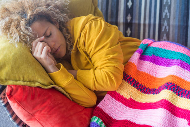 Lonely adult beautiful woman sleep at home in day light time - tired and stressed out people concept sleeping on the couch  - colors lifestyle people relaxing concept stock photo