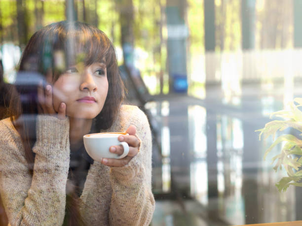 Lonely Asian woman drinking hot coffee in glasses house cafe looking out side from window waiting for someone stock photo