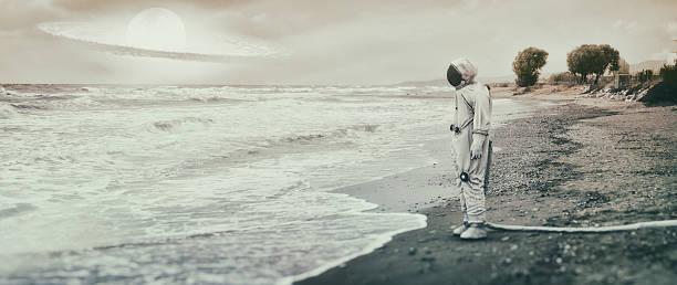 lonely astronaut on the beach - landscape crazy stock-fotos und bilder