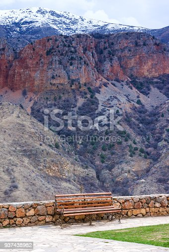 Lonely bench at territory of Medieval armenian Noravank monastery complex against red mountains, Armenia