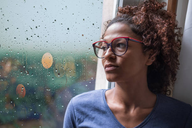 Lonely black woman near window thinking about something Sad african american girl looking out of the window on rainy weather sadness stock pictures, royalty-free photos & images