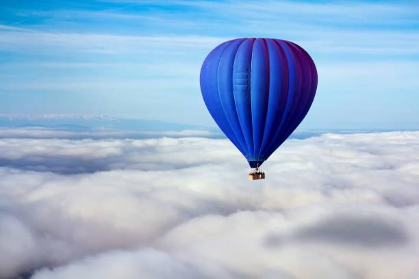 une montgolfière bleu solitaire flotte au-dessus des nuages. leader concept, solitude, réussite, victoire - montgolfière photos et images de collection