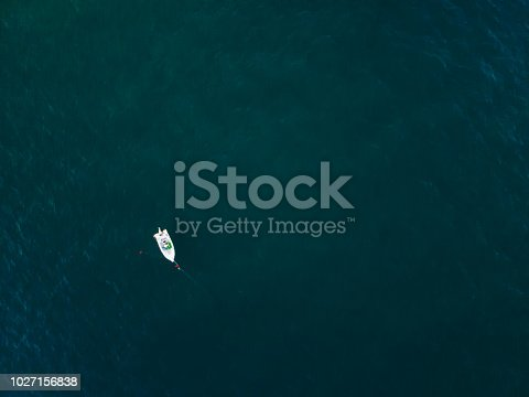 811600544 istock photo Lonely boat anchored in the sea 1027156838