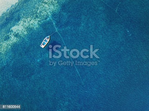 811600544 istock photo Lonely boat anchored in the sea 811600544