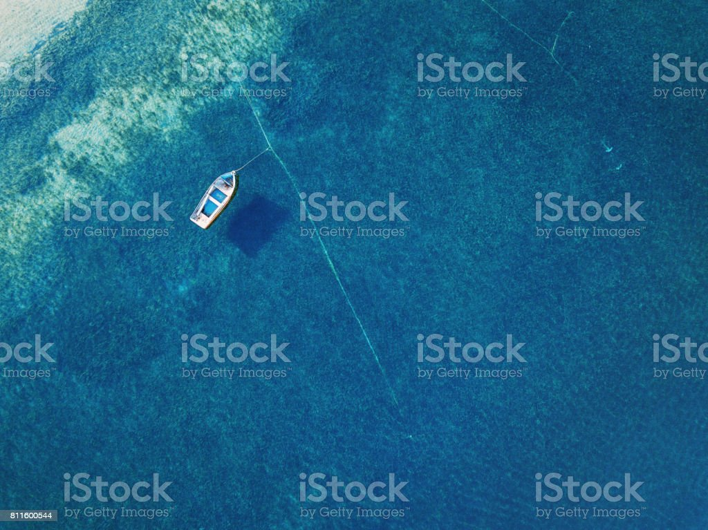 Lonely boat anchored in the sea stock photo