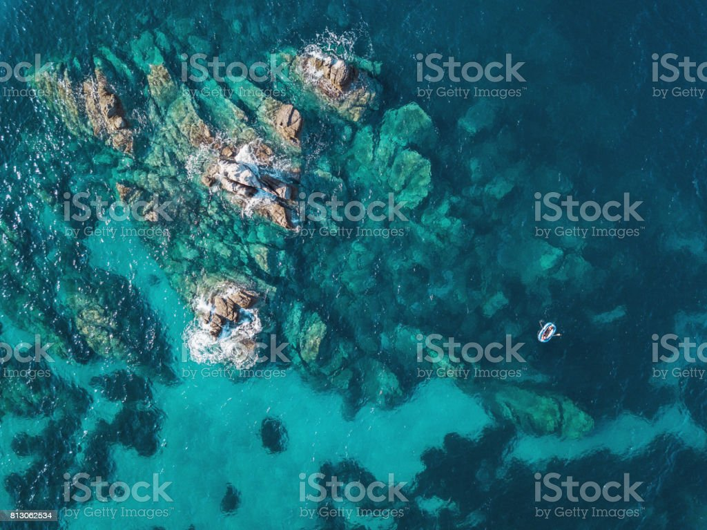 Lonely boat near reefs Aerial view of blue sea, rocks and a small boat Aerial View Stock Photo