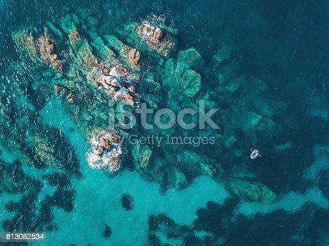 Aerial view of blue sea, rocks and a small boat