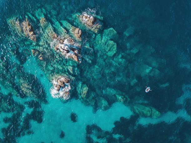 Lonely boat near reefs stock photo