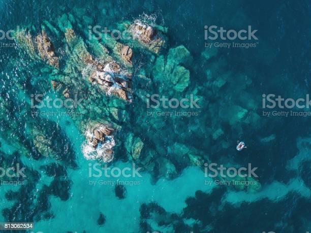 Lonely Boat Near Reefs Stock Photo - Download Image Now