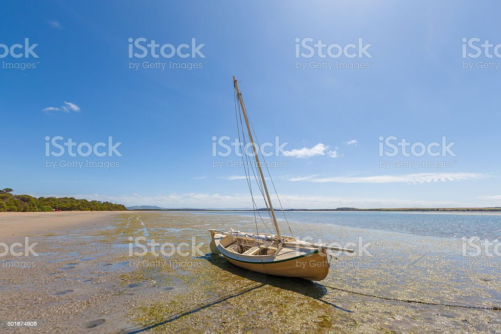 Lonely boat on sun drenched beach at Sandy Point, Australia stock photo
