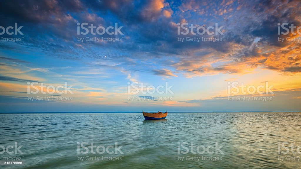 Lonely boat on the Baltic Sea at sunset. stock photo
