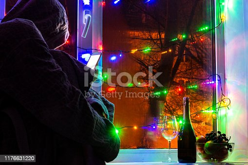 lonely bored man with a smartphone, waiting for the new year. Front and background blurred with bokeh effect